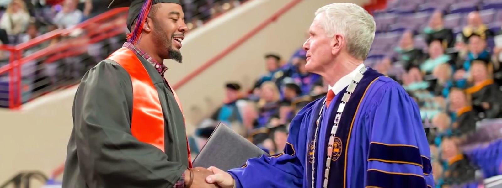 Clemson student graduating shakes professor's hand.