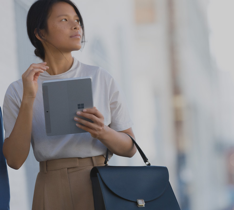 woman on a city street holds her Surface Go in Tablet Mode in one hand