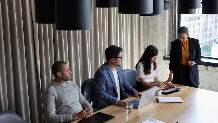 People in a meeting sit around a conference table with their Surface devices