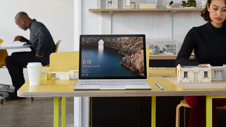 Front-facing view of Surface Book on a yellow table at an architecture firm's office