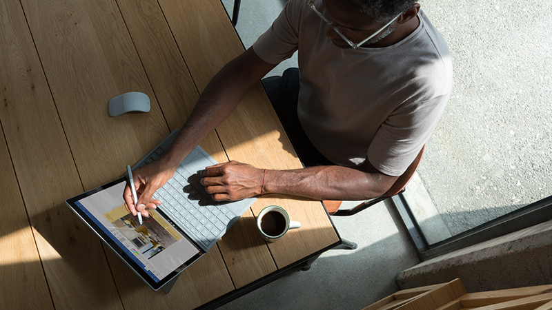 Man uses Surface Pen on Surface Pro with LTE Advanced in laptop mode at a wooden table, next to a Surface Arc Mouse and a cup of coffee.