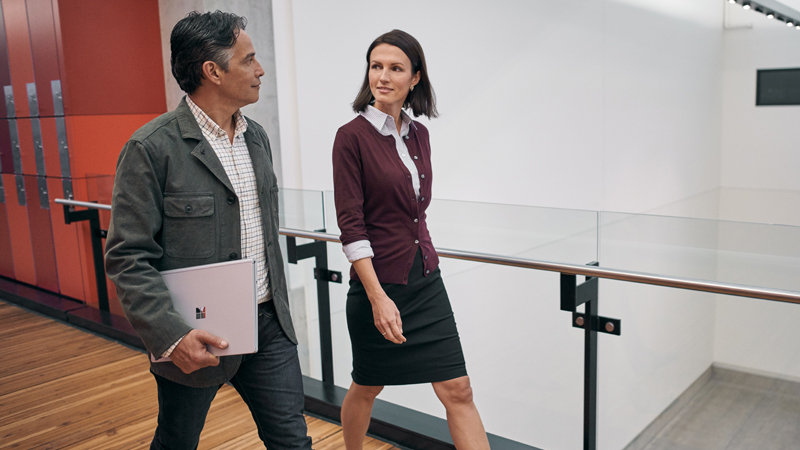 Man carries Surface Book in right hand, and walks alongside woman in workplace.