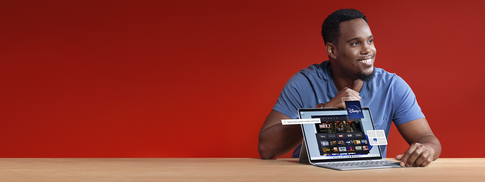 A man sits at a desk with his laptop in front of him. Digital elements such as the Disney+ app icon, and Snap Layouts magically come of his screen.