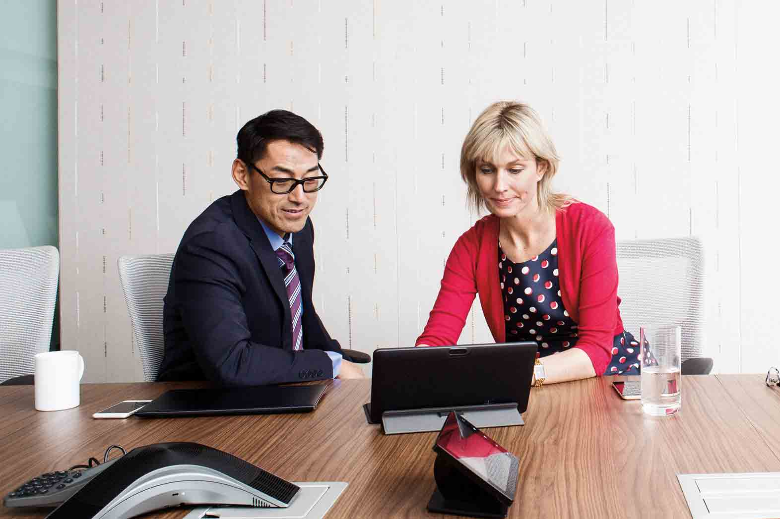 Two employees meet in a conference room and discuss their new surface tablets