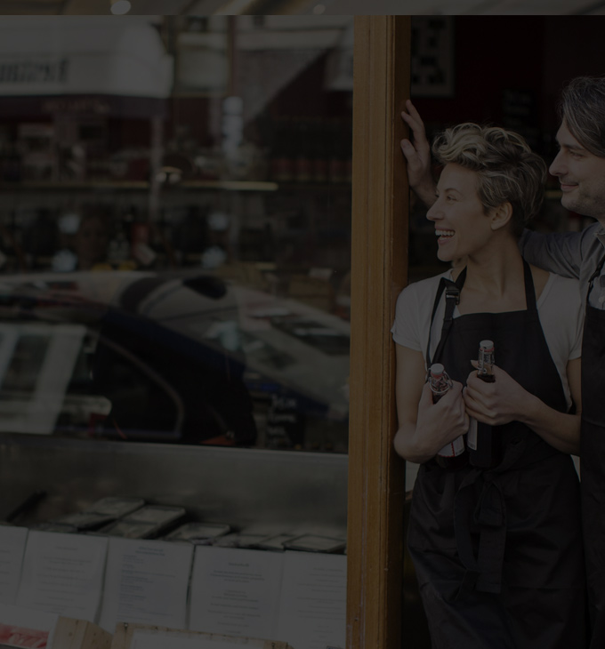 A man and woman standing in doorway of their business. Office 365 is built for your business.