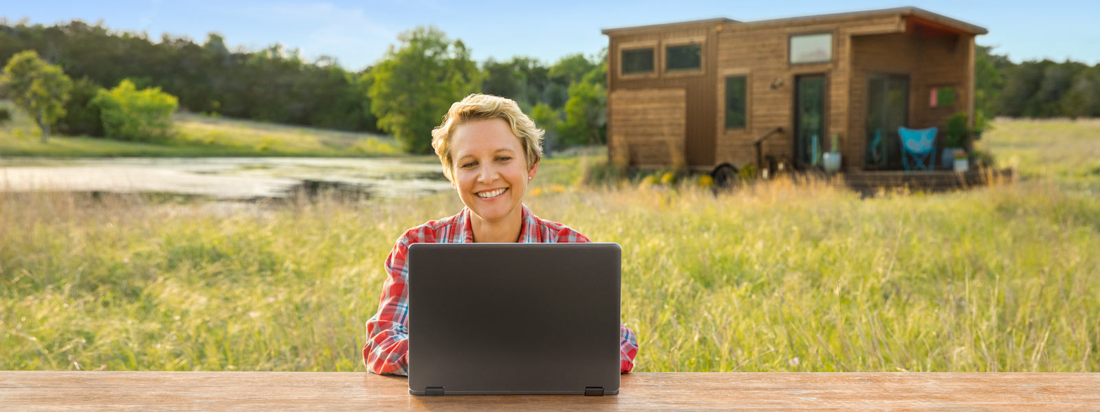 Woman sitting on a bench in the countryside enjoying her Always Connected PC