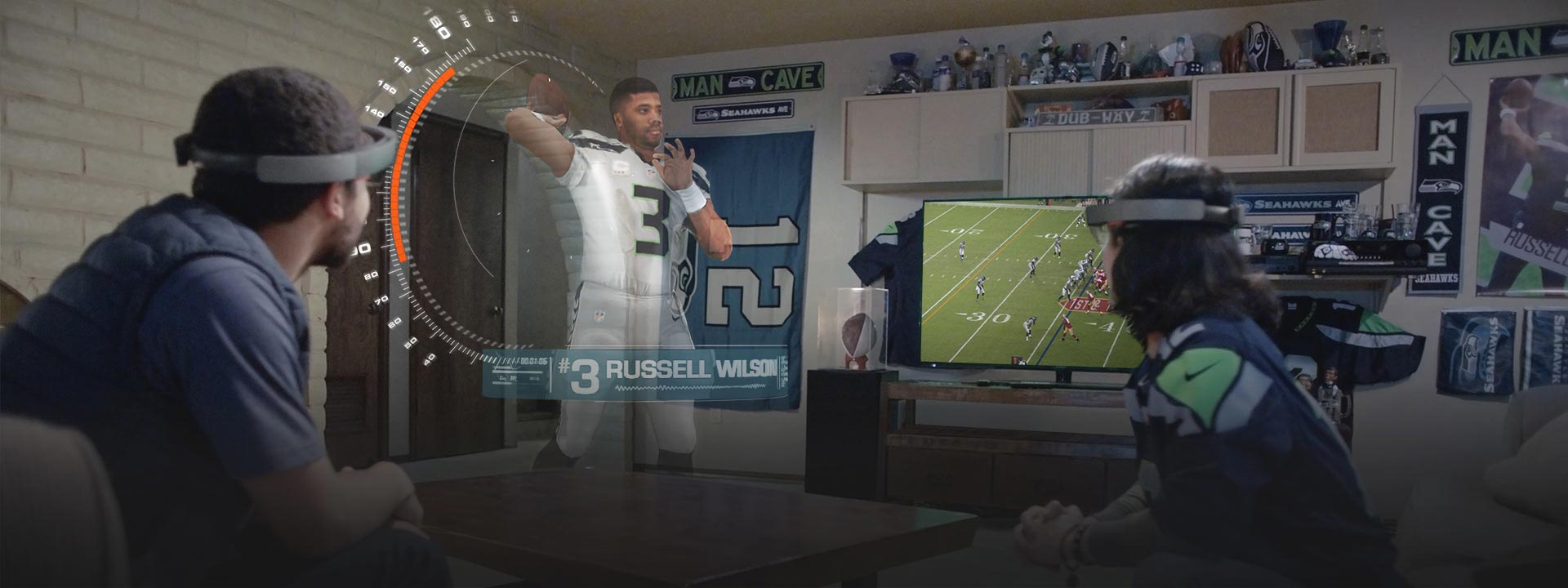Two people wearing Microsoft HoloLens watch a football game and a hologram of Russell Wilson.