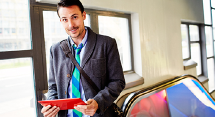 A man standing near the top of an escalator, holding a tablet and smiling.