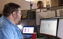 man looking at powerpoint on computer desktop