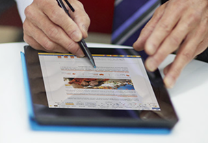 A person using a pen on a tablet, learn about Office 365 business-class mobile apps