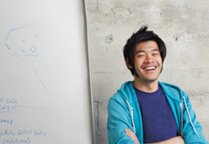A smiling man next to a whiteboard, learn about Office 365 Developer Patterns and Practices