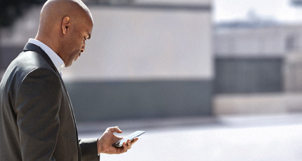 A man in a suit standing outside, working on his phone with one hand.