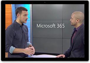 Image of two people standing and talking in front of a sign that reads Microsoft 365