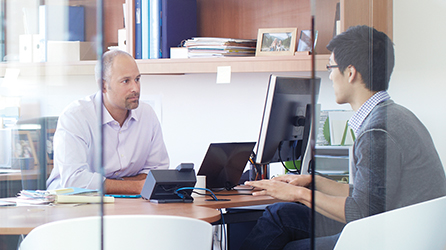 Two men having a meeting in an office, a destination page that includes a form you can complete to download the free ebook titled '5 Questions Business Decision Makers Should Be Asking Their Security Teams'
