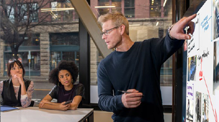 A man giving a presentation to two others in a conference room, download the Better Together eBook to learn more about the collaborative features of Office 365.