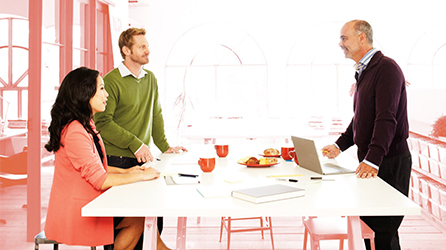 Coworkers meeting around a table, get the eBook Innovation is a Team Sport by downloading the file now