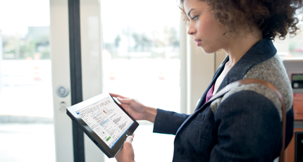 A woman standing up in an office using Office 365 on a tablet.
