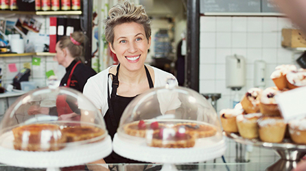 A woman behind a bakery counter, download the eBook about What I wish I knew: 5 Small Business Owners Share Success Secrets by completing the form on the registration page