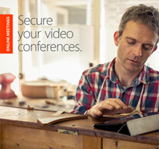 Man in a workshop looking at a tablet computer, get the Secure your video conferences eBook