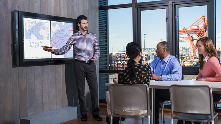 Two women and two men in a conference room, one man is presenting on a Surface Hub