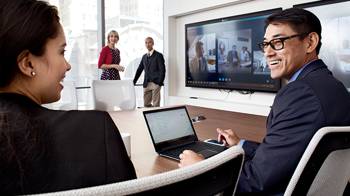 Several people meeting and talking in a conference room with remote meeting attendees appearing on a screen