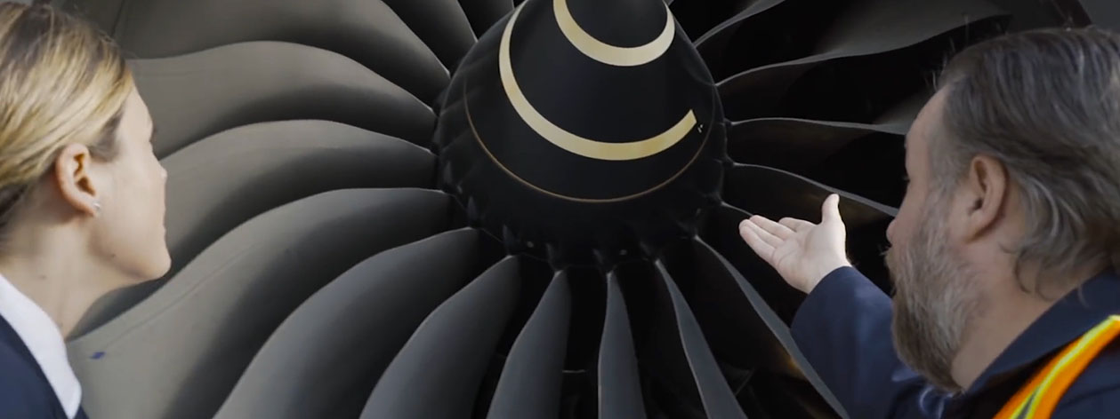 Man pointing towards a plane engine