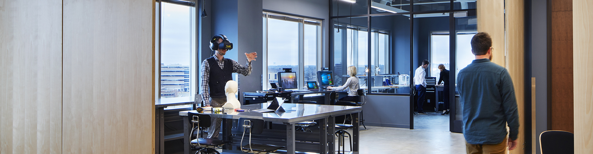 Man using HoloLens and woman sitting at a computer.