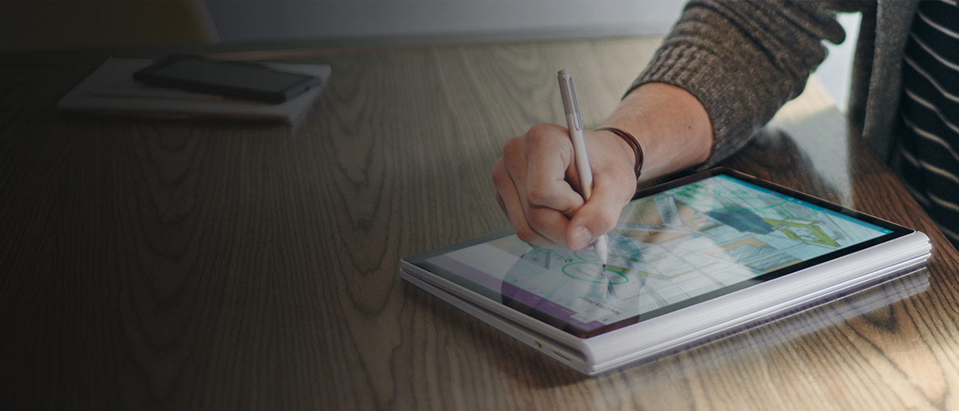 Person using a stylus to draw on folded-open Surface Book