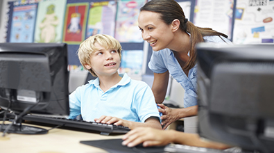 A teacher looking over the shoulder of a male youth at a computer screen