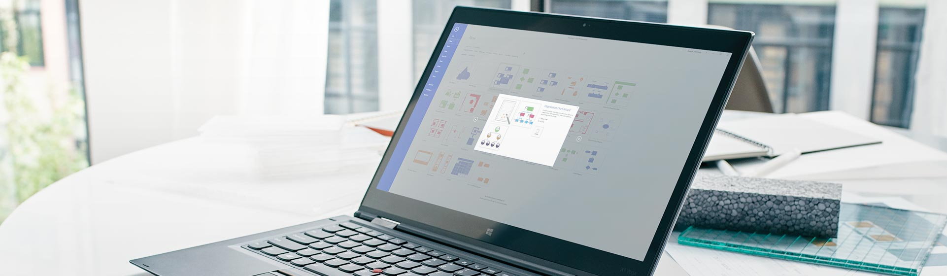 A tablet screen displaying an animation of how to create an organizational chart using a wizard in Visio