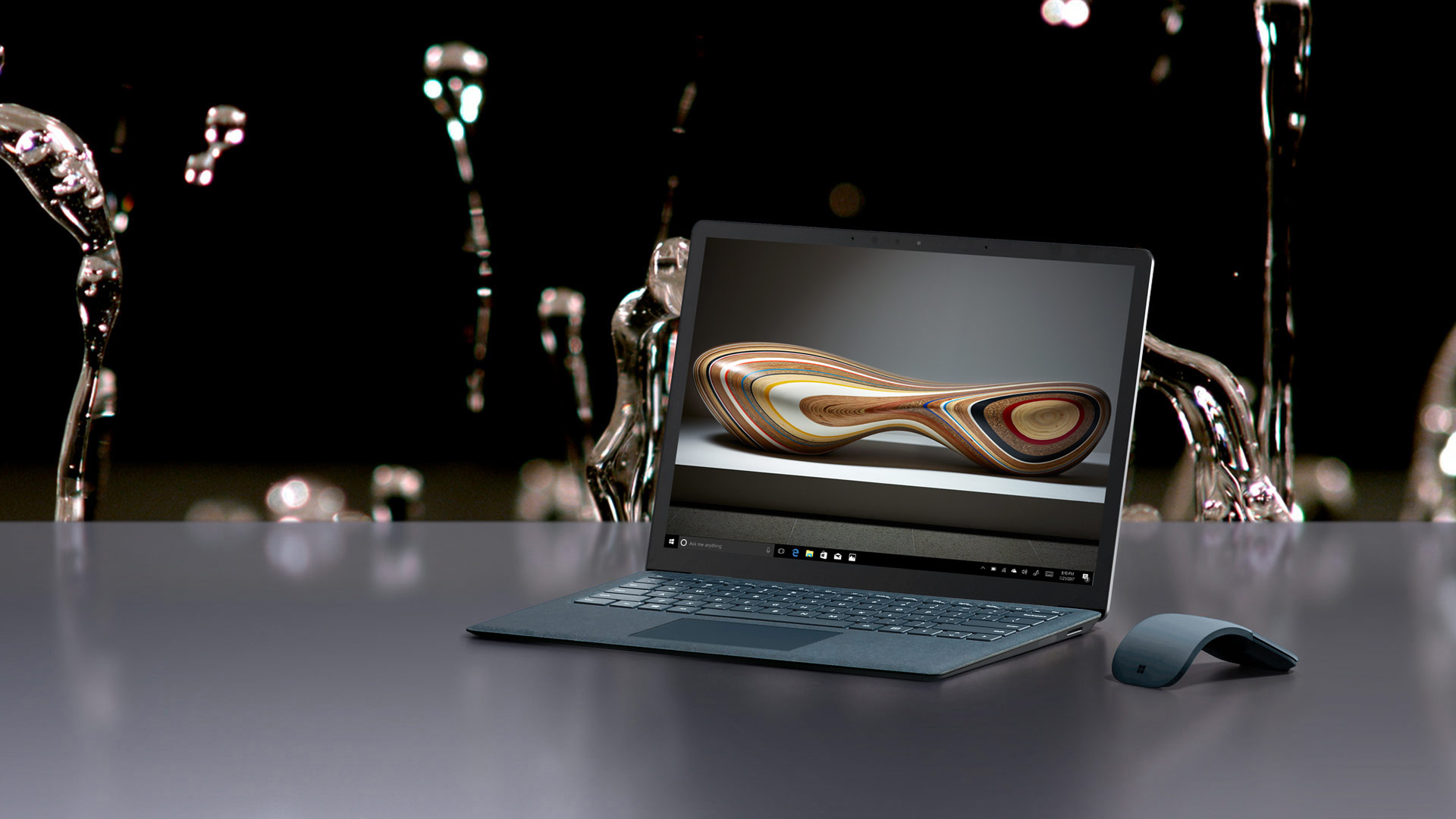 Surface Laptop with mouse against a water backdrop.