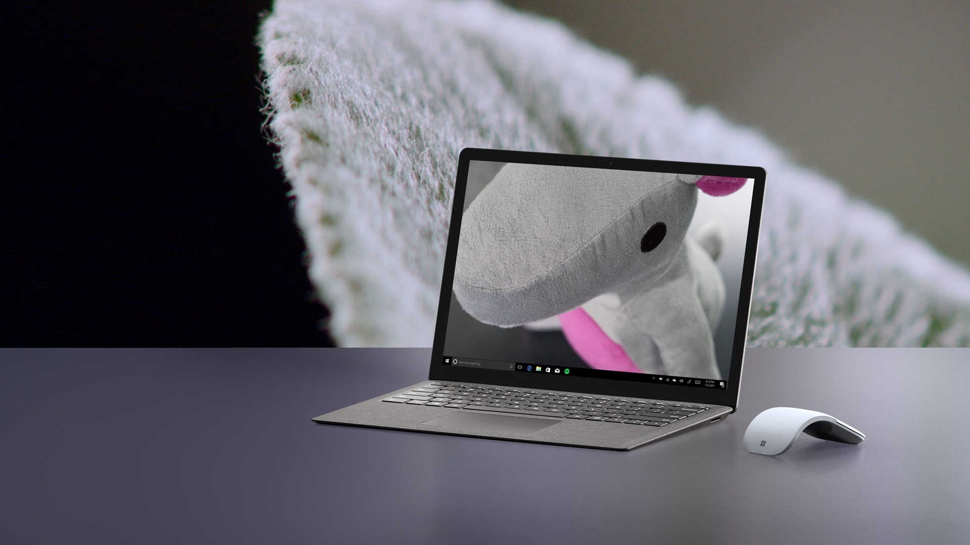 Surface Laptop with mouse against a sage leaf backdrop.