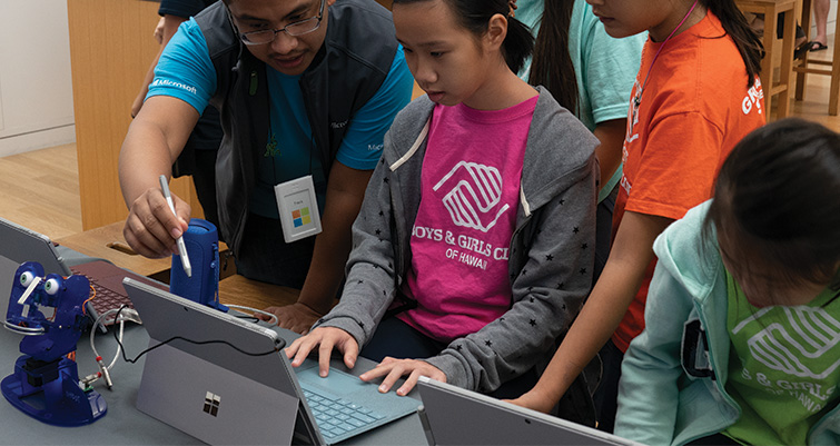 Male Microsoft store employee teaching three female students in Ohbot camp.