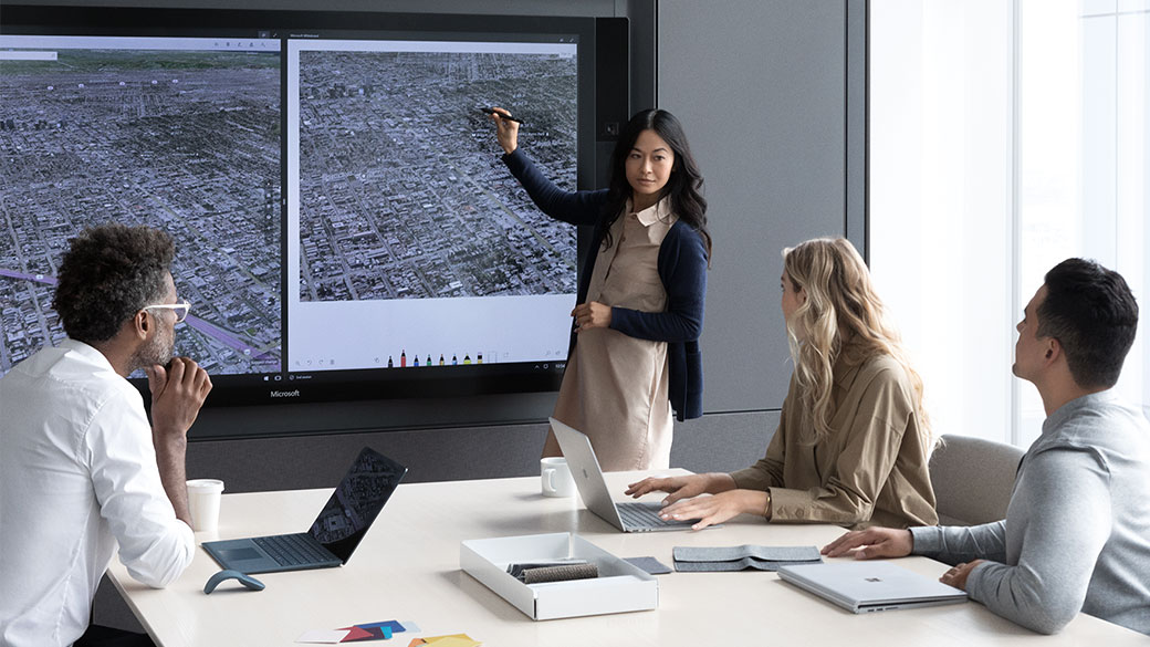 Woman uses Surface Pen on a Surface Hub to show her colleagues something on a map in the Microsoft Whiteboard app.