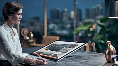 Woman looking at her Surface Studio in studio mode on a desk in a high-office setting with a city visible through windows in the background