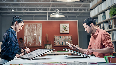 Man and woman working across from each other both with the Surface studio in studio mode