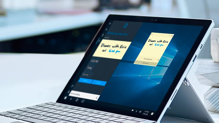 Surface Pro 4 in laptop mode on desk with sticky notes visible on the screen