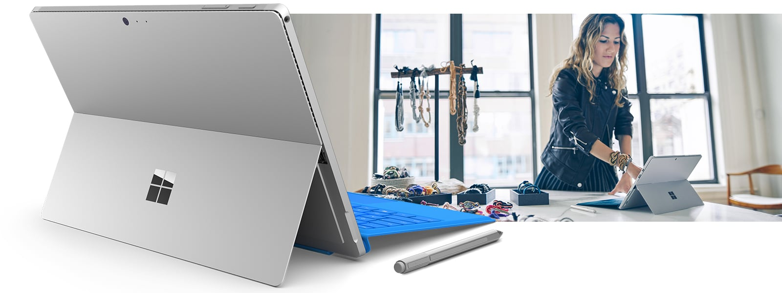 Surface Pro 4 in laptop mode, as seen from behind with an image of woman touching Surface Pro 4 screen on a desk in a jewelry workshop