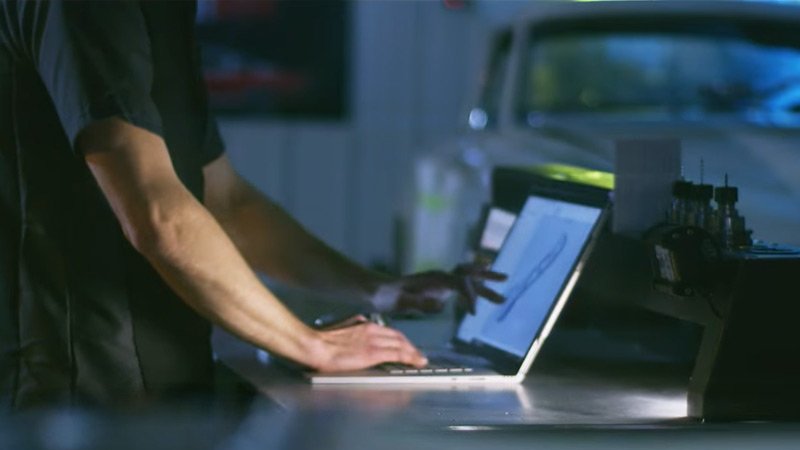 Man uses touchscreen on Surface Pro 4 with a car in the background
