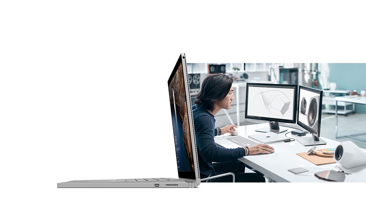 Man working at desk with Surface Book connected to keyboard, mouse and two external monitors