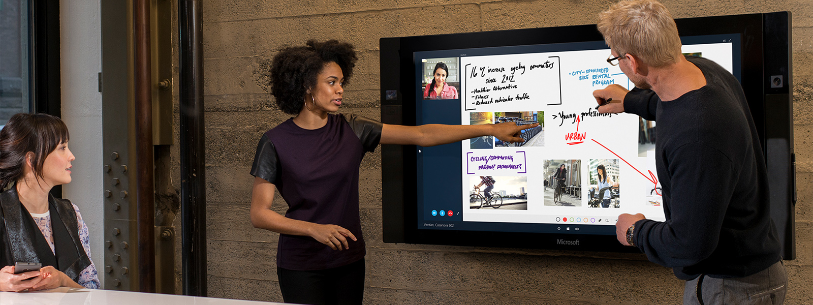 Woman and man use touchscreen on Surface Hub in conference room.
