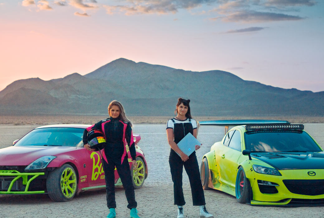 Cache, a video director and editor, and Collete, a professional race car driver, stand side by side in front of two multi-colored race cars in a desert