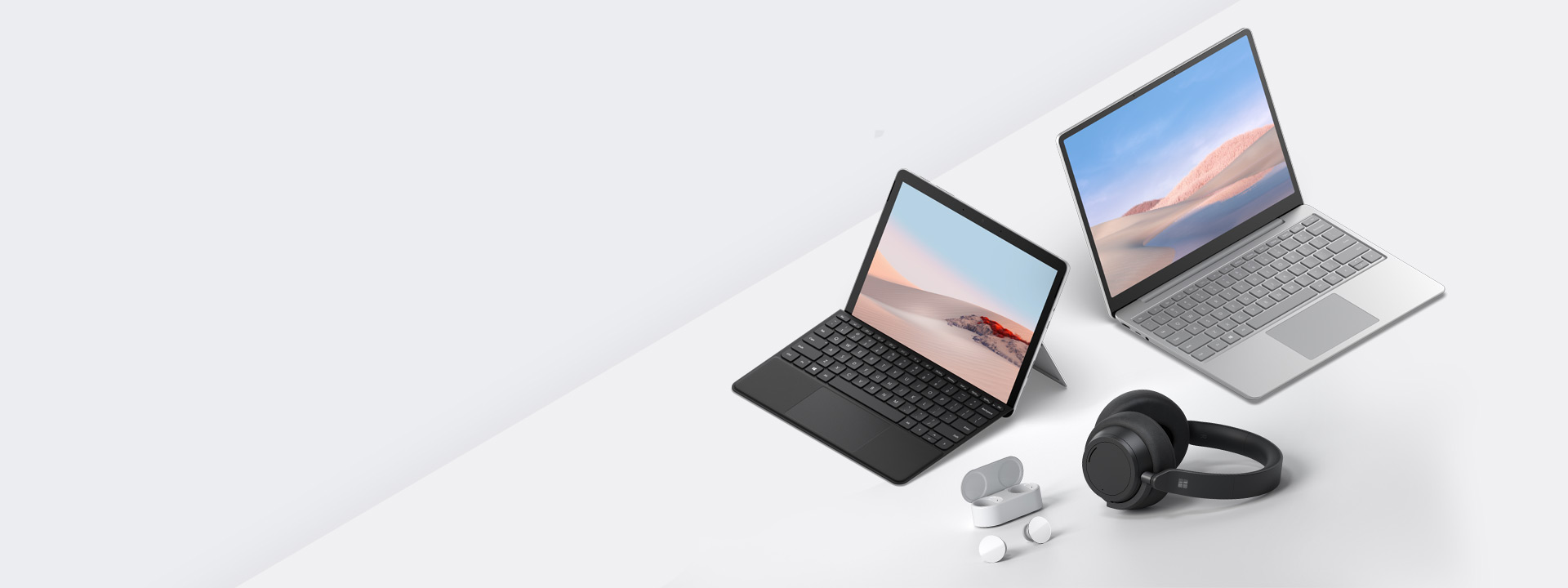 Image shows Surface Laptop Go and Surface Go 2 with earbuds and headphones.