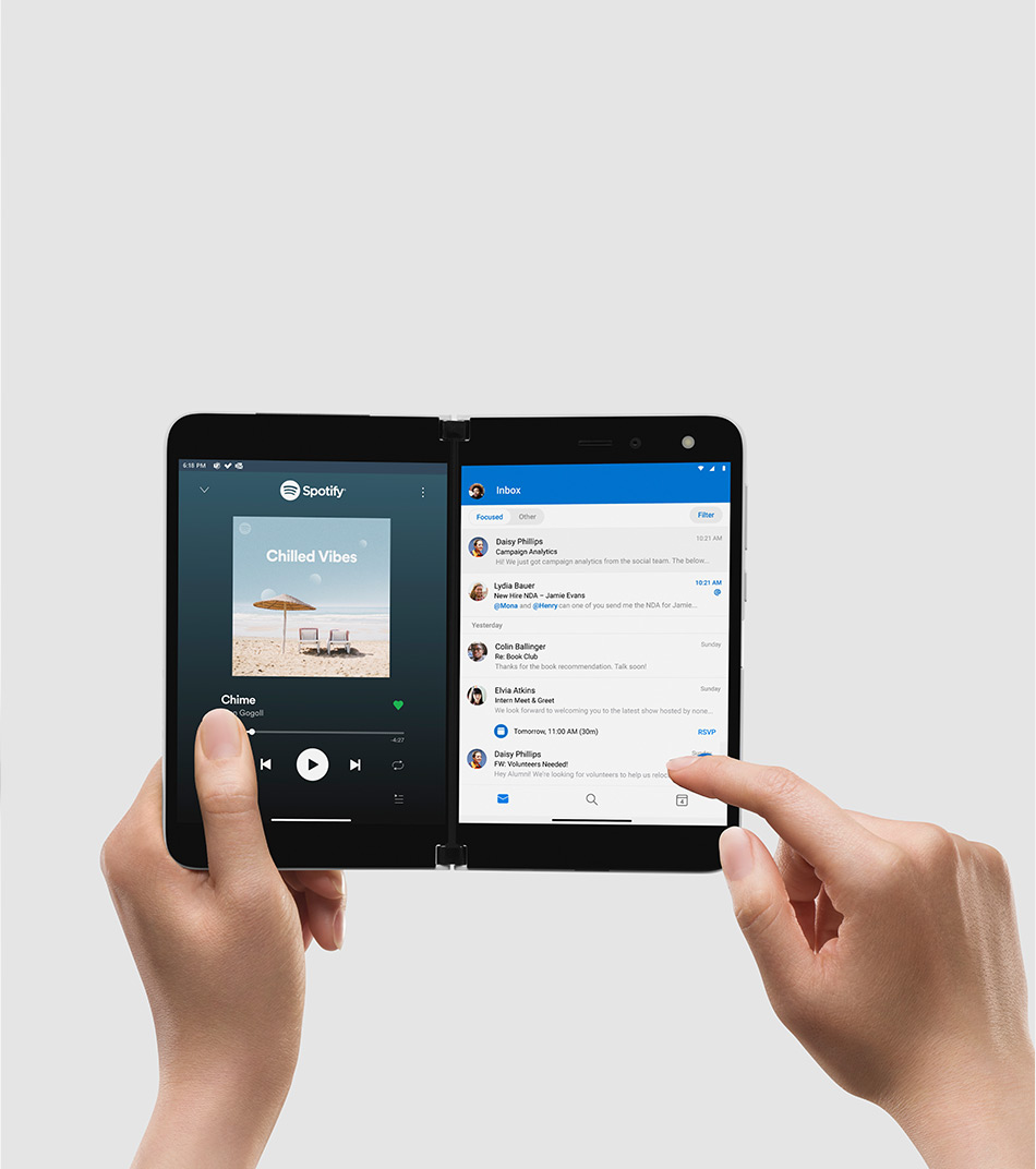 Surface Duo in book mode held by a pair of hands showing Spotify and Outlook