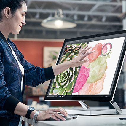 MAN USING SURFACE STUDIO AS A DESKTOP.