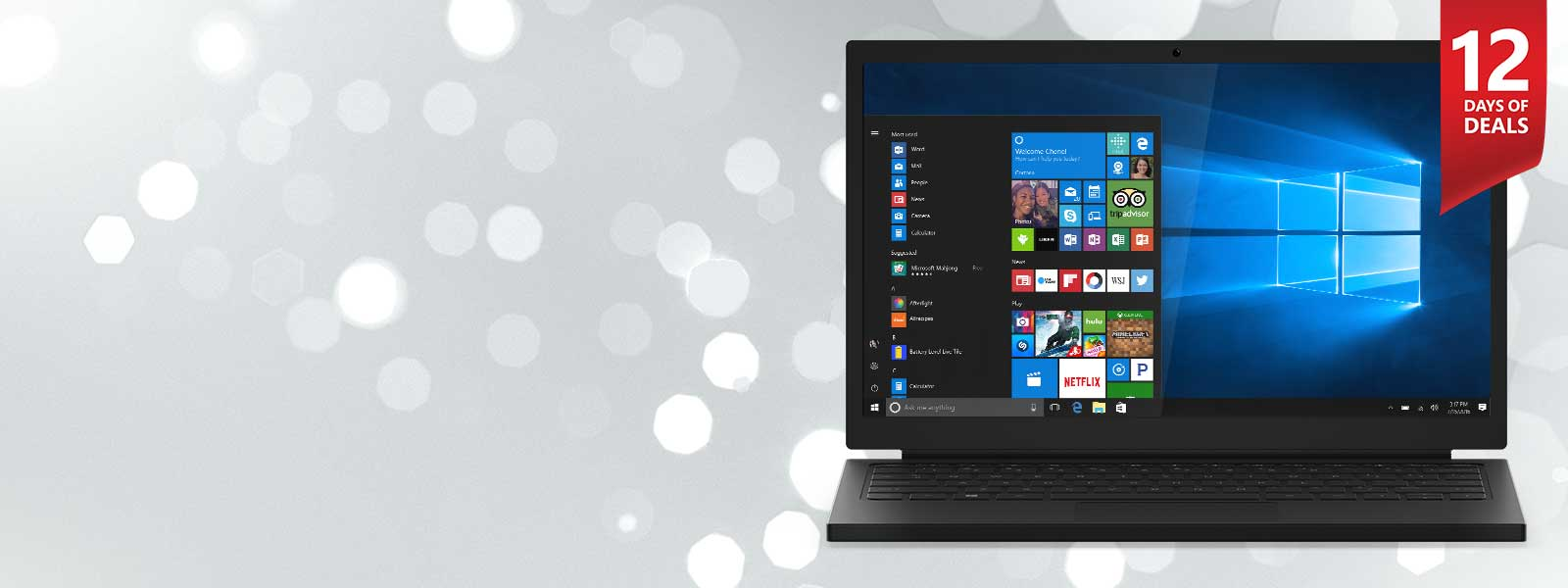 Laptop facing front with Windows start menu open on screen with festive sparkles behind it on a light grey background