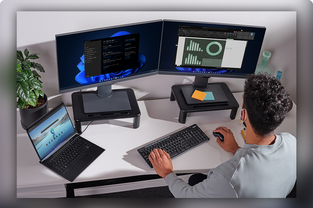 A man at a workstation with two computer monitors and a laptop