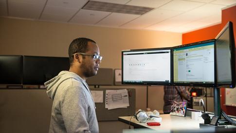 A Man looking at Windows 10 Pro across 3 monitors