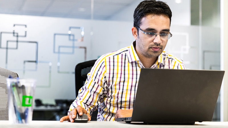 Man in glasses working at a desk with a laptop
