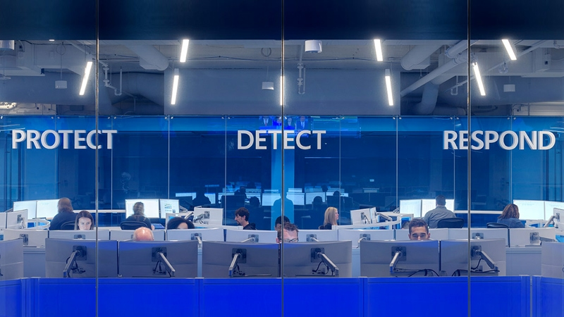 Security office window with people in office cubicles